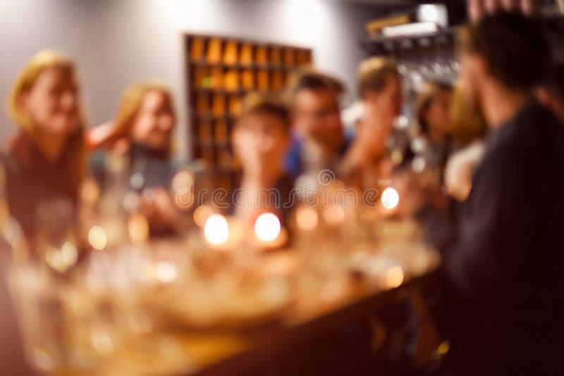 Resuma al grupo borroso de amigos que se encuentran en el restaurante Fondo borroso de la gente caucásica que se divierte, comien fotos de archivo