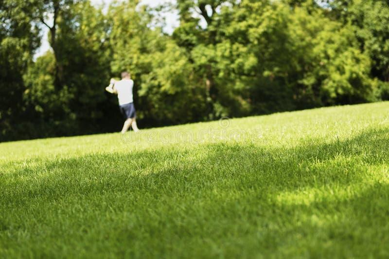 Resuma al hombre que juega la bola y el palo en parque en hierba verde imagenes de archivo