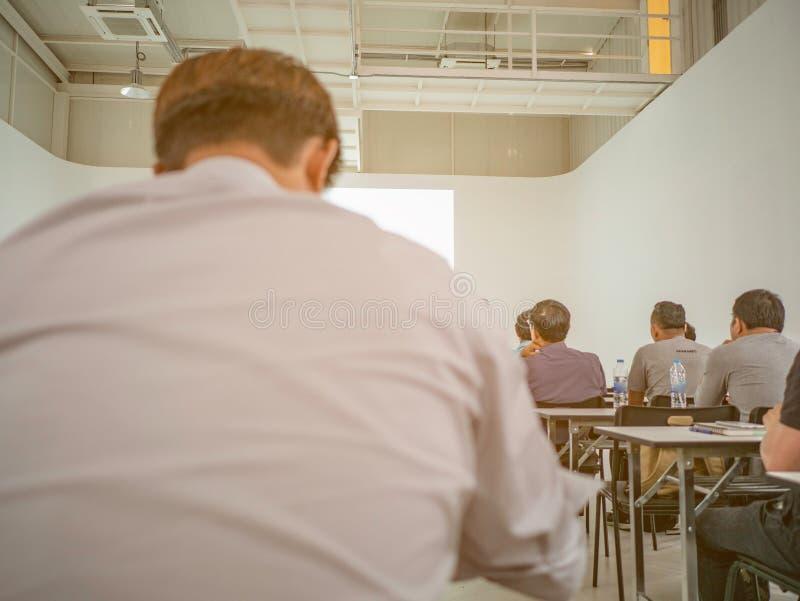 Resuma la foto borrosa de la sala de conferencias o de la sala de seminarios con el fondo del asistente fotos de archivo