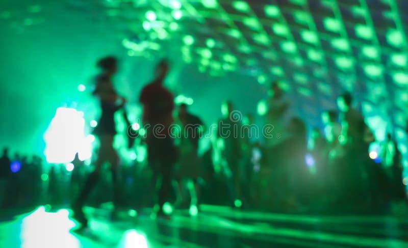 Resuma a la gente borrosa que se mueve encendido y que baila en el club de la música foto de archivo