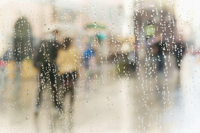 Resuma las siluetas borrosas de la gente con los paraguas en día lluvioso en ciudad, dos personas vistas a través de las gotas de imagenes de archivo