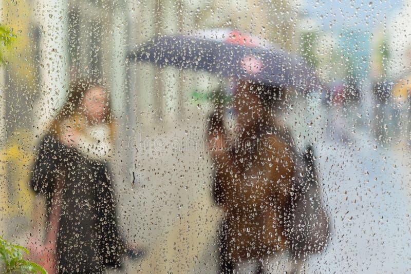 Resuma las siluetas borrosas de la gente con los paraguas en día lluvioso en ciudad, dos muchachas vistas a través de las gotas d fotos de archivo libres de regalías