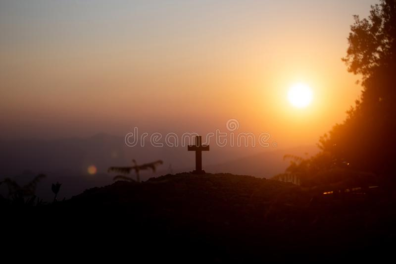 Resurrection concept:Crucifixion Of Jesus Christ Cross At Sunset. Faith of christian concept: Spiritual prayer hands over sun shine with blurred beautiful sunset royalty free stock photos