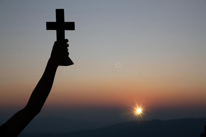 Resurrection concept:Crucifixion Of Jesus Christ Cross At Sunset. Faith of christian concept: Spiritual prayer hands over sun shine with blurred beautiful sunset royalty free stock photo