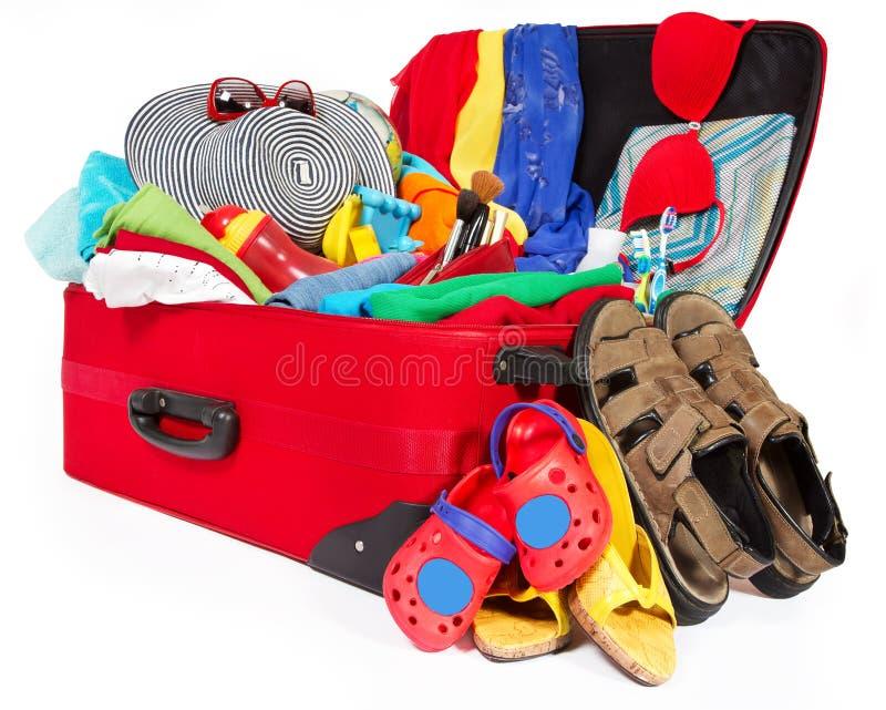 Resväska öppet packat loppbagage, familjpåse mycket av kläder arkivfoto