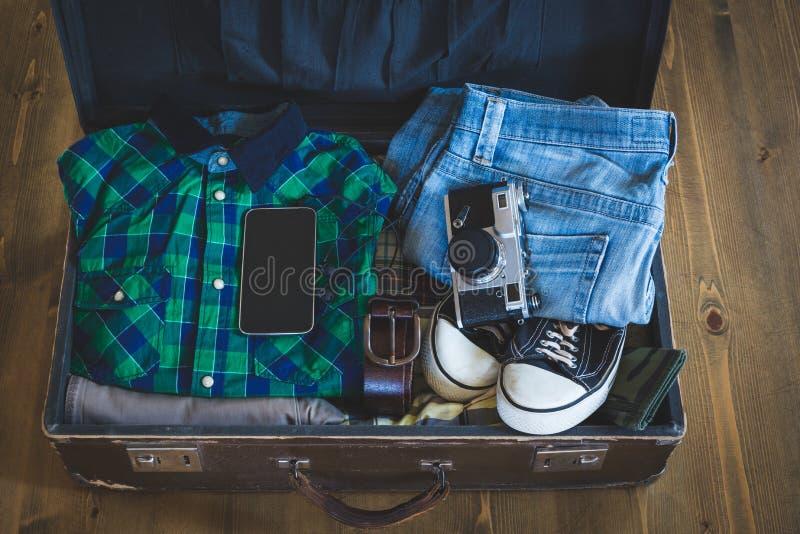 Resväska för emballage för tappninghipsterhandelsresande öppen på ett träbräde med kläder, film-kameran och mobilen royaltyfri bild