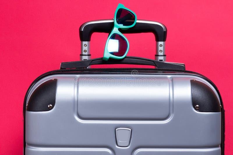 Resväska med solglasögon på rosa bakgrund Sommarloppbegrepp royaltyfri foto