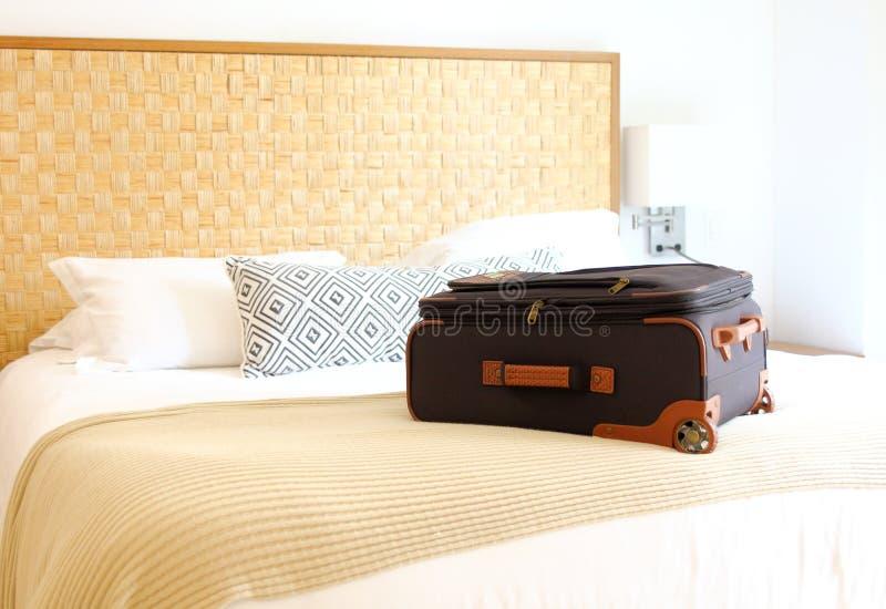 resväska på sängen inom ett hotellrum royaltyfri bild