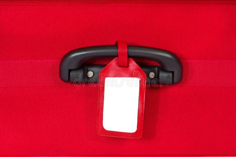 Resväskaetikett, tom IDetikett på röd loppbagagepåse arkivfoton