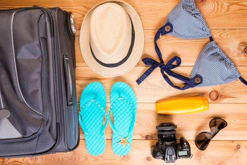 resväskan och ordnar till objekt för att en kvinna ska koppla av royaltyfri foto