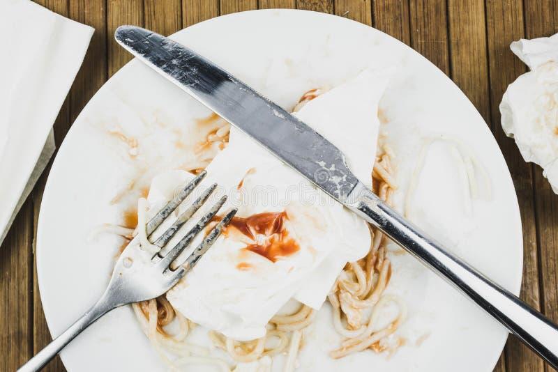 Resztki spaghetti, rozwidlenie i nóż na białym talerzu, fotografia stock