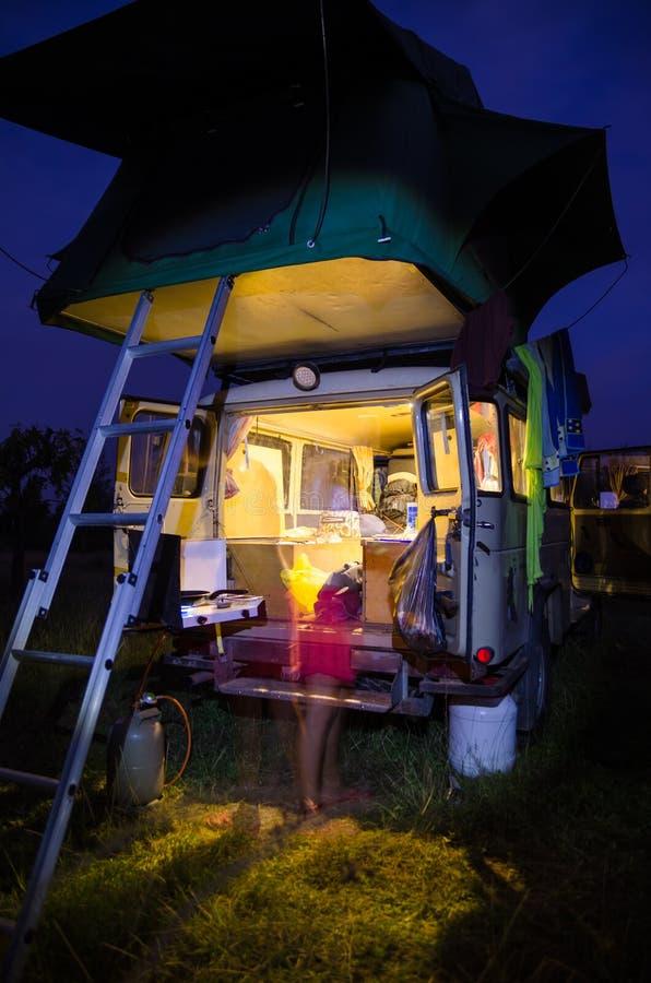 A retaguarda do veículo de acampamento 4x4 com a barraca e o movimento da parte superior do telhado borrou o cozimento da jovem m foto de stock royalty free