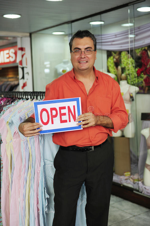 Retail business: store owner with open sign. Retail business: proud store owner with open sign stock image