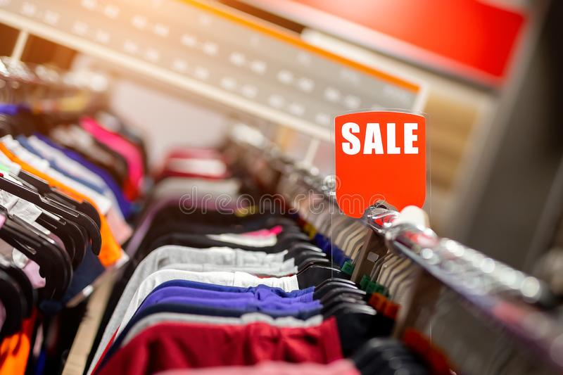 Retail clothes store clearance. Garment shop with various bright youth casual wear at discount price. Wear hangers and red SALE. Signboard. Seasonal sales on stock images