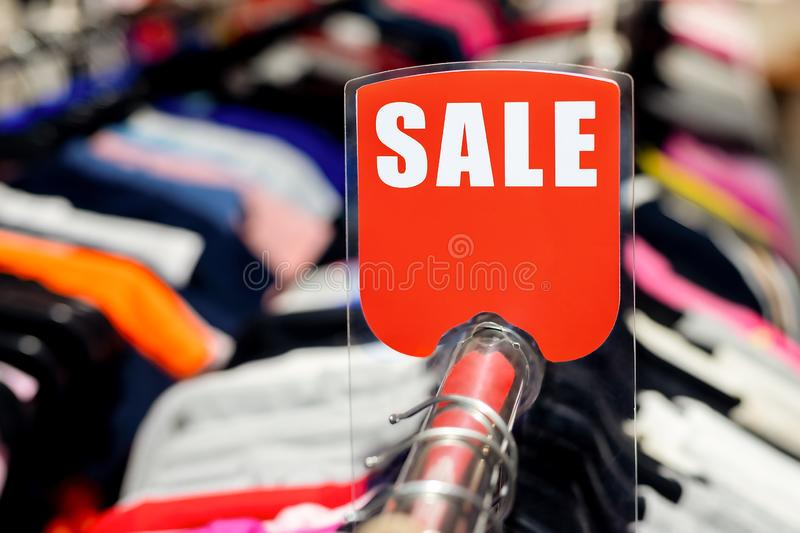 Retail clothes store clearance. Garment shop with various bright youth casual wear at discount price. Wear hangers and red SALE. Signboard. Seasonal sales on royalty free stock photo