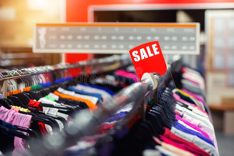 Retail clothes store clearance. Garment shop with various bright youth casual wear at discount price. Wear hangers and red SALE. Signboard. Seasonal sales on royalty free stock image