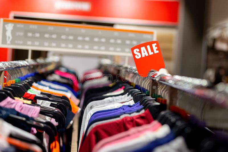 Retail clothes store clearance. Garment shop with various bright youth casual wear at discount price. Wear hangers and red SALE. Signboard. Seasonal sales on stock photos