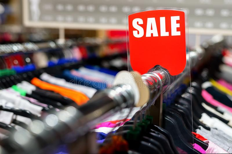 Retail clothes store clearance. Garment shop with various bright youth casual wear at discount price. Wear hangers and red SALE. Signboard. Seasonal sales on stock photography
