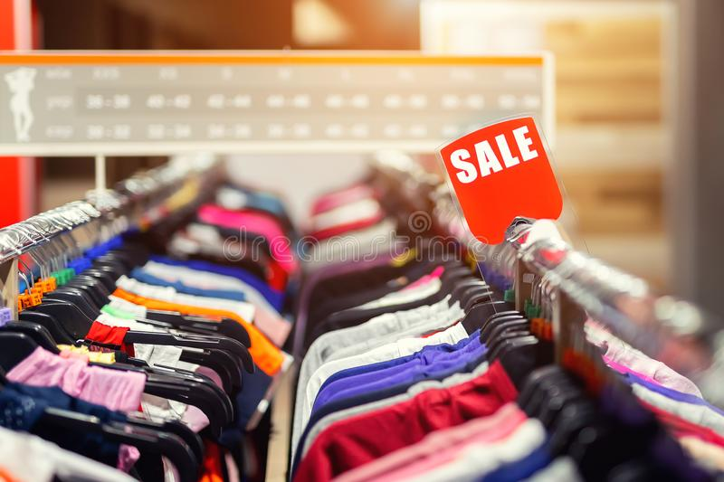 Retail clothes store clearance. Garment shop with various bright youth casual wear at discount price. Wear hangers and red SALE. Signboard. Seasonal sales on stock image