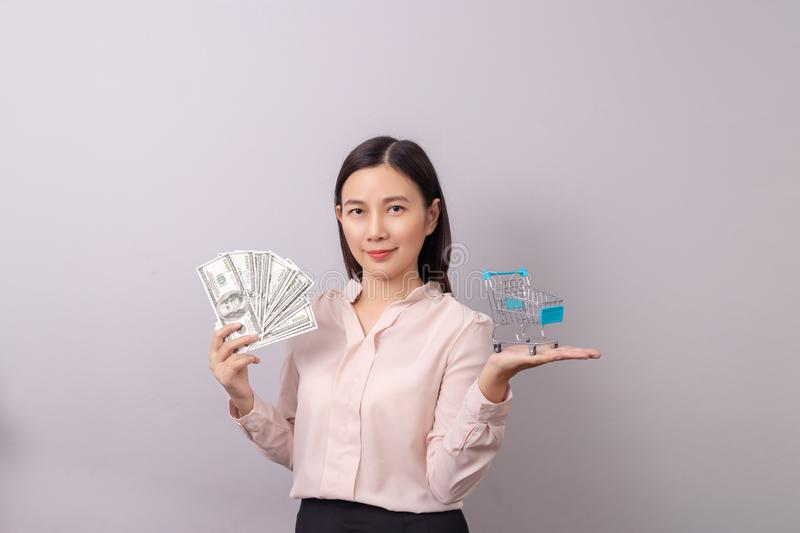 Retail commercial business concept, Asian beautiful woman holding banknote money in hand and shopping cart in another hand stock images