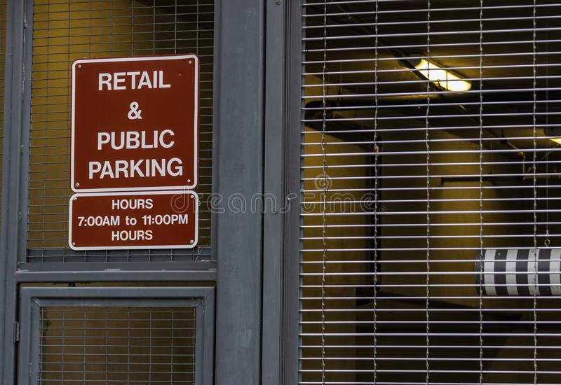 Retail and public parking sign next to a steel fence. And door royalty free stock photo