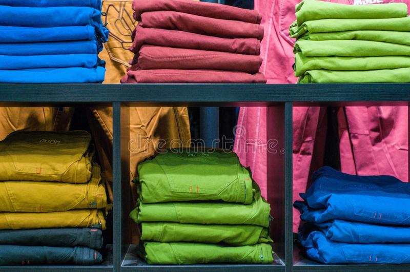 New pants on shelf in the store. Retail sales. Shopping center. New clothes. Colorful background design stock photos