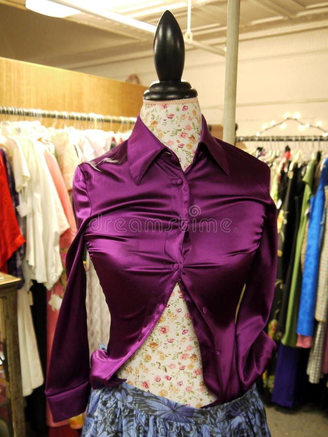 Retail: second hand clothes purple shirt. Purple satin shirt on mannequin in second-hand used clothing store stock image