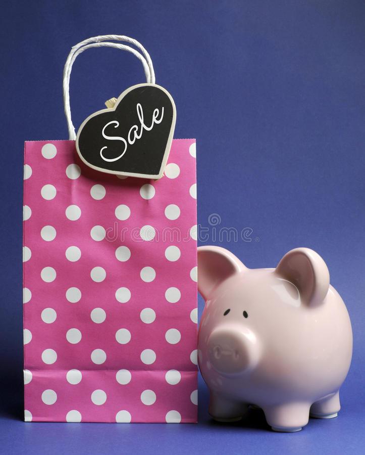 Retail Shopping Sale promotion with pink polka dot bag and piggy bank. With Sale message on heart shape blackboard tag on blue background stock images