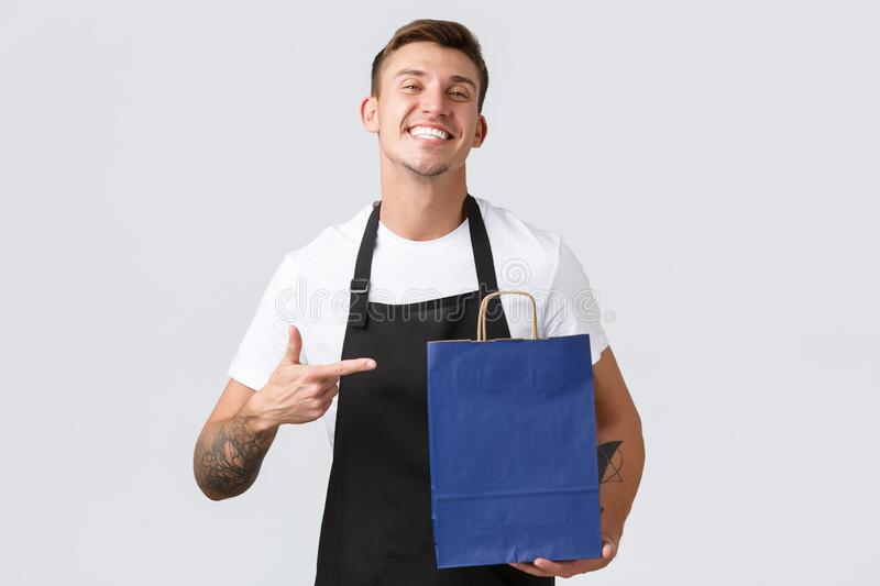 Retail store, shopping and employees concept. Handsome cheerful salesman in shop, bakery staff pointing finger at eco stock image