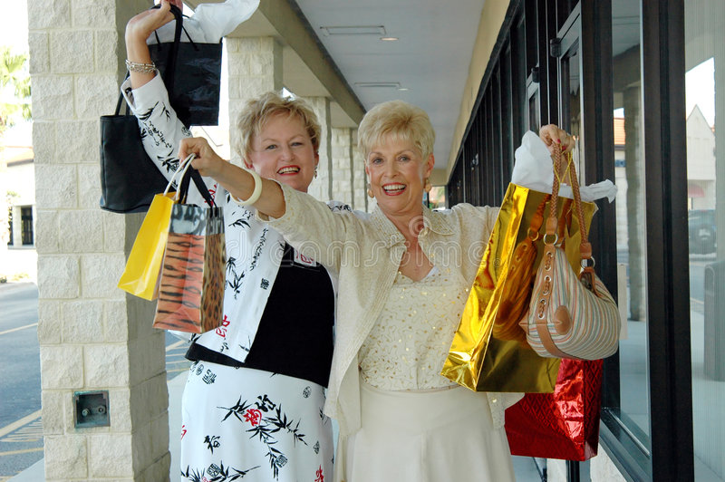 Retail Therapy. Two senior women shopping together having fun holding up lots of shopping bags stock images