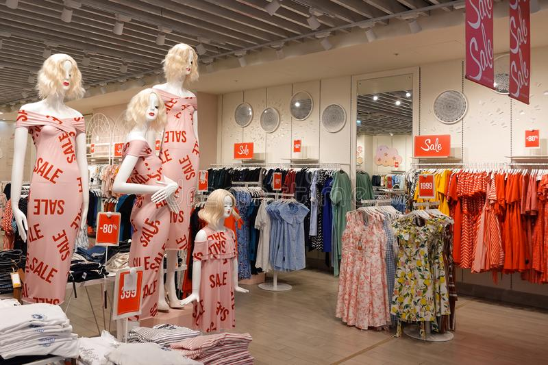 Retail women`s clothing store sale display with four mannequins in foreground. Retail women`s clothing store sale display that inludes  red sale signage and a royalty free stock images