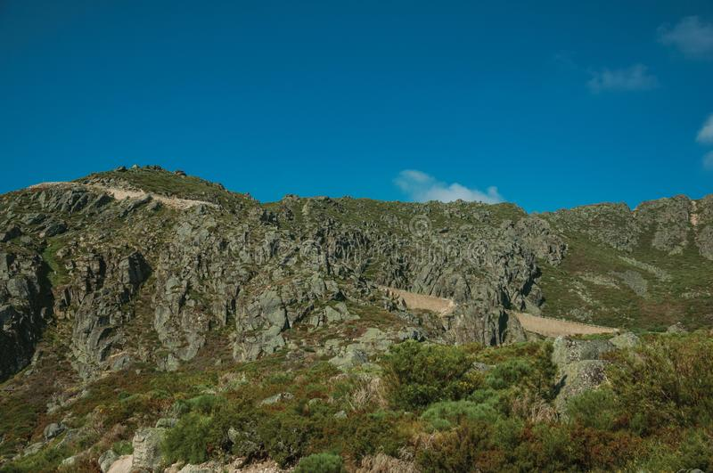 Retaining wall of road passing through rocky landscape royalty free stock photography