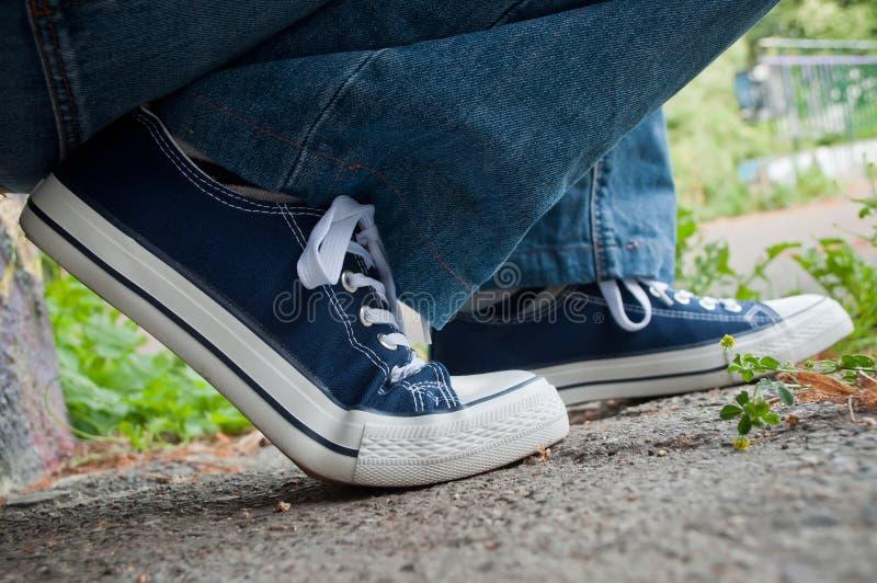 Retalho com das sapatilhas e da calças de ganga azuis do verão fotografia de stock