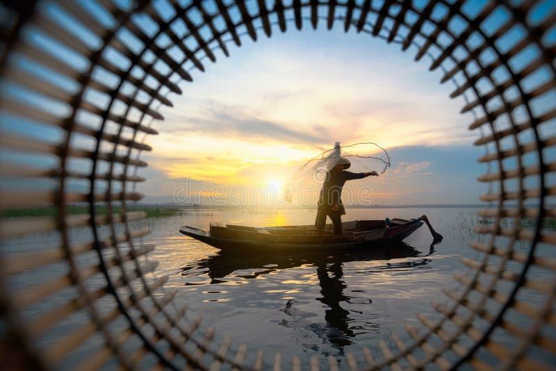 Rete da pesca di lancio del pescatore della siluetta durante fotografie stock libere da diritti