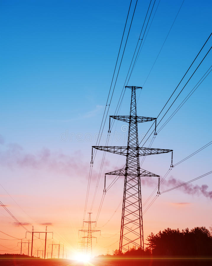 Rete di distribuzione di energia - piloni di elettricità contro il tramonto arancio e giallo fotografia stock libera da diritti