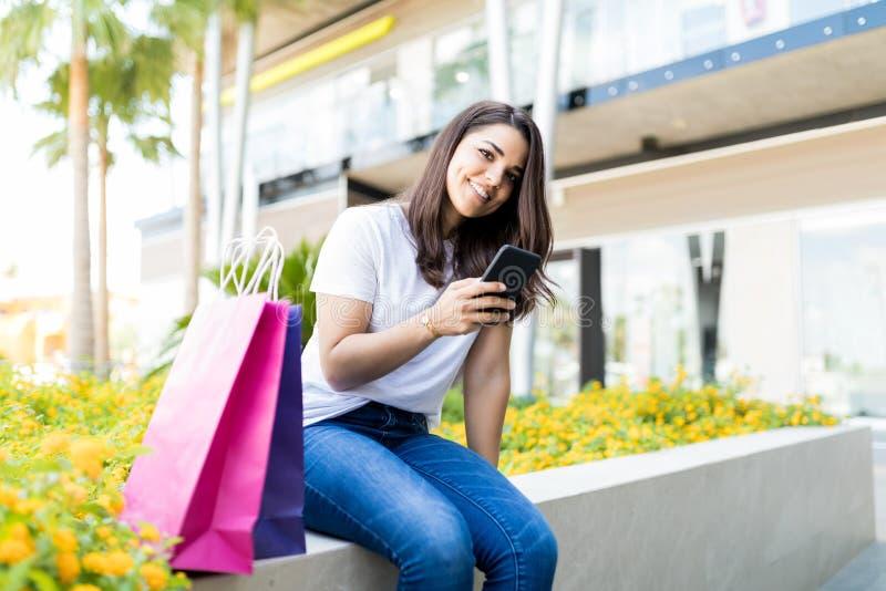 Rete sociale sorridente della donna di Shopaholic sul telefono cellulare Outsi fotografie stock libere da diritti