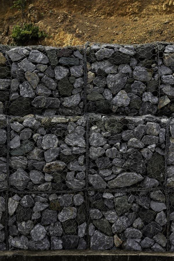 Retenci?n de la pared de piedra al lado del camino Cerca o pared de la protecci?n hecha de gabions con las piedras Pared de piedr imagen de archivo