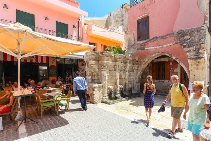 Rethymno, isla Creta, Grecia, - 1 de julio de 2016: La gente está comiendo en el café situado cerca de la fuente de Rimondi en la foto de archivo libre de regalías