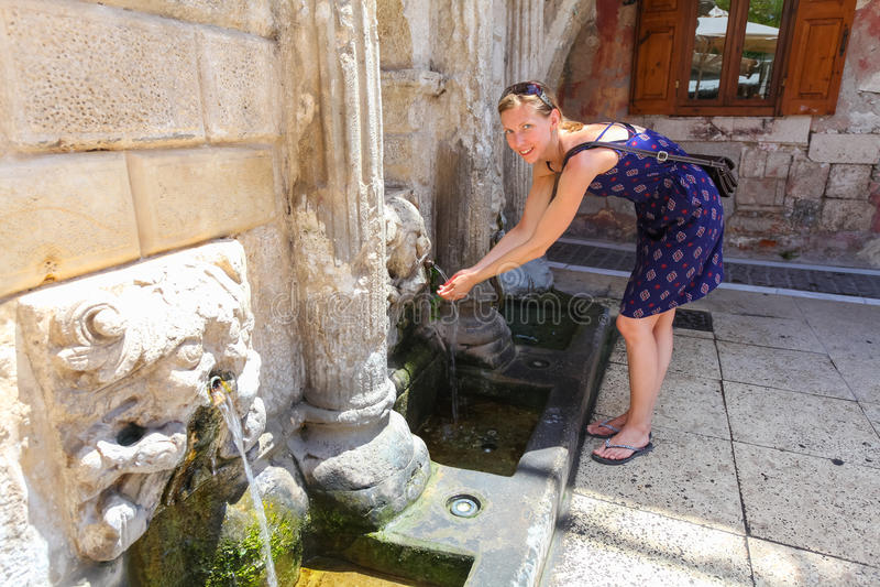 Rethymno, isla Creta, Grecia, - 1 de julio de 2016: La mujer joven está bebiendo la agua fría clara de la fuente de Rimondi en la imagen de archivo