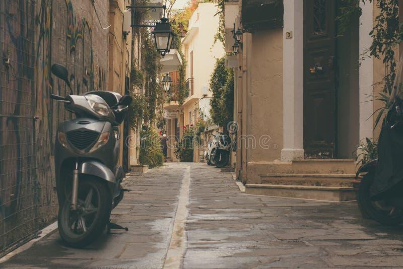 Rethymno, isola Creta, Grecia, - 8 giugno 2017: vecchio motorino parcheggiato e un'entrata principale d'annata della parte della  immagine stock