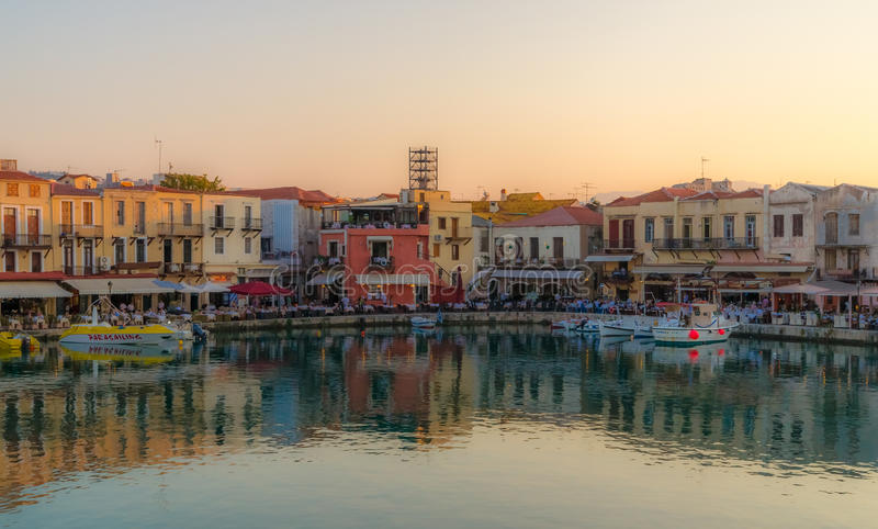 Rethymno water front at sunset. Rethymno, Greece - June 19: People enjoy the sunset at the picturesque water front of Rethymno old town. June 19, 2011, in