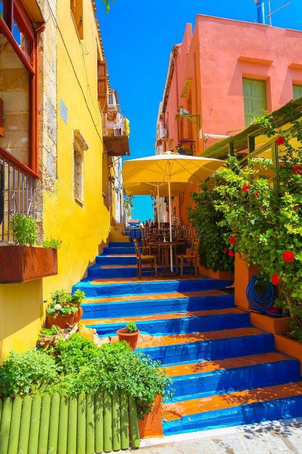 Rethymnon,海岛克利特,希腊, - 2016年7月1日:舒适小克里特岛咖啡馆和五颜六色的台阶在好的克里特岛房子之间 免版税图库摄影