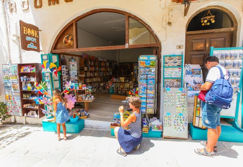 Rethymnon ö Kreta, Grekland, - Juli 1, 2016: Familj nära `en för fläck för bok för souvenirlager`, Det finns modern tar fotointel royaltyfri fotografi