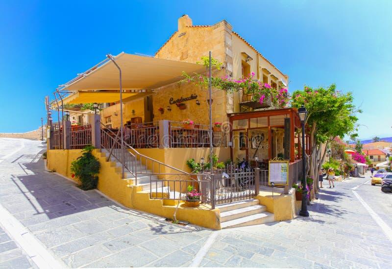Rethymnon, остров Крит, Греция, - 1-ое июля 2016: Уютное малое критское кафе с открытой верандой с цветками и красочными лестница стоковая фотография