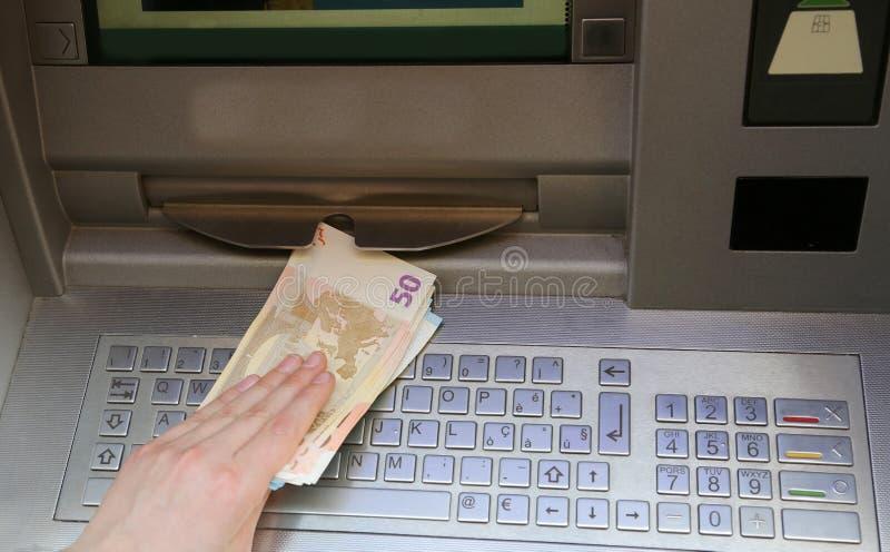Retira euro- cédulas do dinheiro de um ATM de um banco europeu foto de stock royalty free