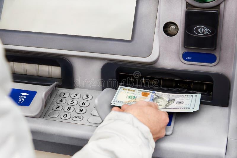 Retirada de dinheiro nos dólares de um ATM fotografia de stock royalty free