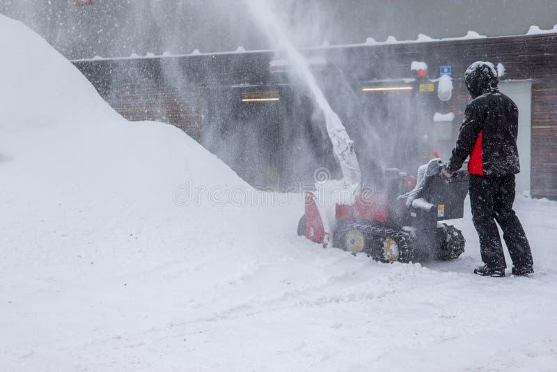 Retirada de la nieve con un ventilador de nieve imagenes de archivo
