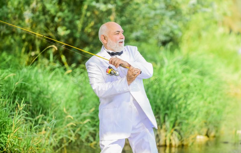 Retired businessman. Elegant bearded man fishing. Luxury life concept. Grandpa is my name, fishing is my game. Hobby and. Recreation. Fisherman in formal suit royalty free stock photo