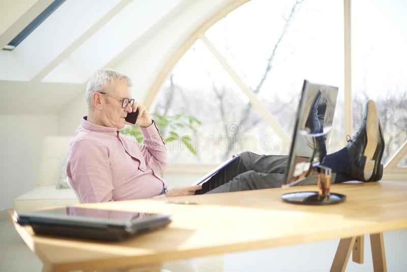 Retired businessman talking with somebody on his mobile phone. Senior businessman using his mobile phone and talking with somebody while sitting in front of royalty free stock photo