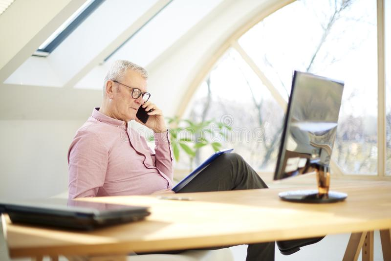 Retired businessman talking with somebody on his mobile phone. Senior businessman using his mobile phone and talking with somebody while sitting in front of royalty free stock photos